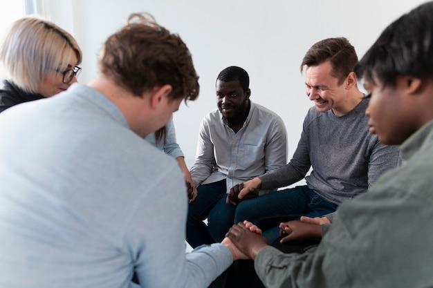 Patients de réadaptation souriants debout dans un cercle et main dans la main