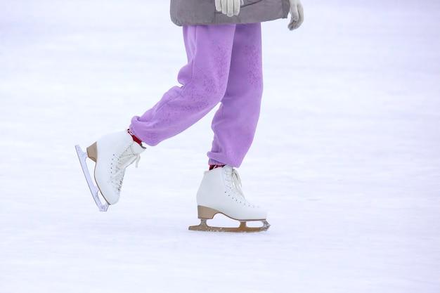Patin à glace jambes de femme sur la patinoire. loisirs et sports d'hiver