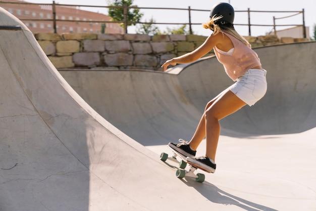 Le patin moderne des femmes urbaines en demi-pipe