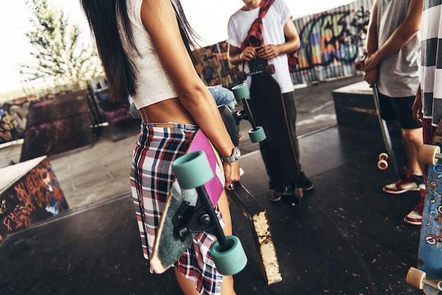 Le patinage est leur vie. gros plan de jeunes gens modernes debout avec des planches à roulettes tout en passant du temps à l'extérieur