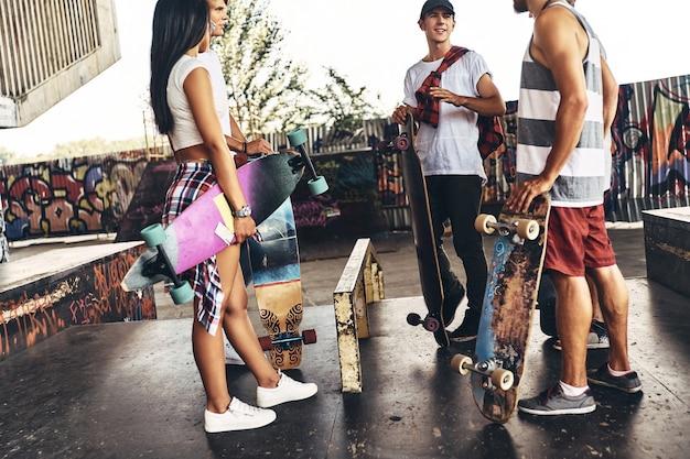 Le patinage est plus qu'un passe-temps. groupe d'amis patineurs discutant en se tenant à l'extérieur