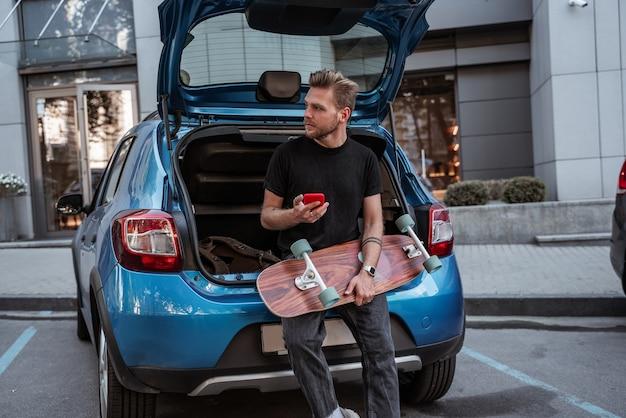 Patineur masculin blond sérieux tenant un longboard assis sur un coffre de voiture sur un parking à l'aide d'un smartphone. habitudes urbaines. concept de sport extrême. notion de communication. concept de vie en ville. concept de loisirs en plein air.