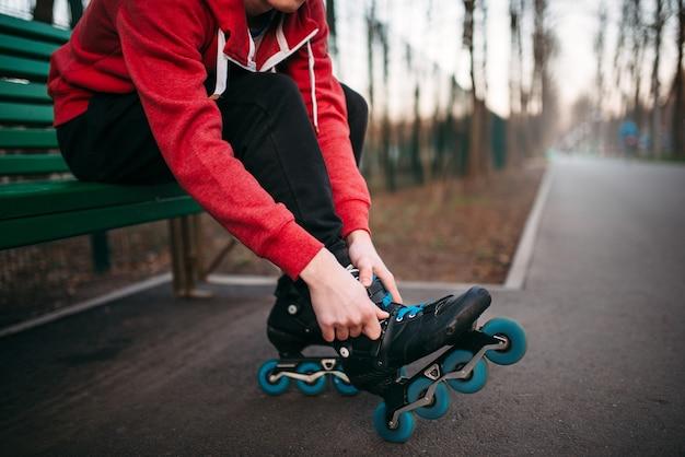 Patineur à roulettes assis sur un banc et patins à lacets