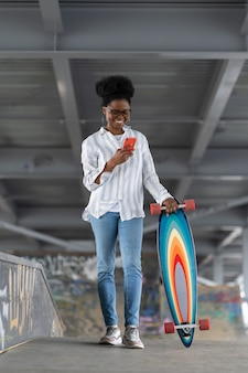 Une patineuse africaine avec un longboard tient la notification des réseaux de lecture de téléphone dans l'espace pour les planchistes