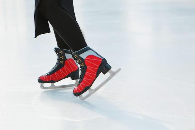 Patineuse artistique sur glace la fille patine sur glace sous le ciel ouvert