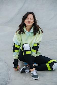 Une patineuse brune en tenue de sport assise sur sa planche sur un sol en béton. elle regarde la caméra.