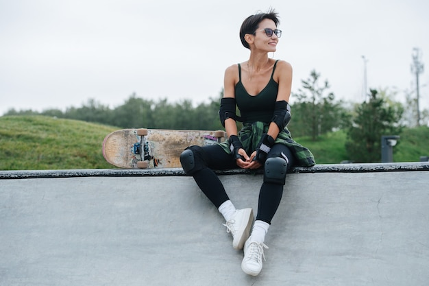 Patineuse joyeuse aux cheveux courts en lunettes de soleil reposant sur un pont, s'amusant. elle porte un équipement de protection. vue frontale. nature en arrière-plan.