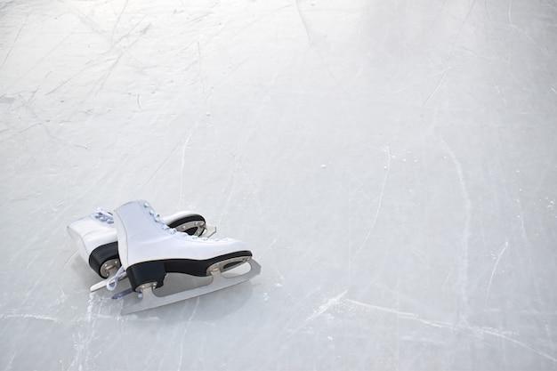 Les patins blancs pour femmes reposent sur la glace. vue depuis le sommet. patinoire de divertissement hivernal
