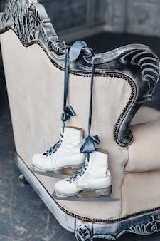Des patins blancs sont suspendus à l'arrière du canapé, utilisés pour le patinage artistique
