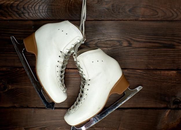 Des patins en cuir blanc pour le patinage artistique sont suspendus à un clou