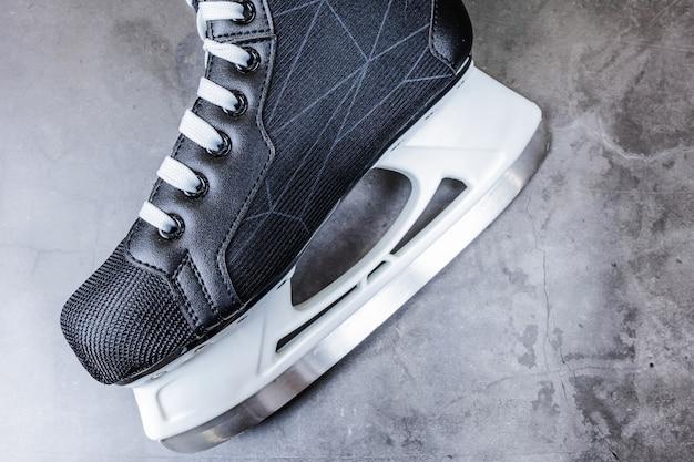 Patins de hockey noirs et blancs pour hommes sur gris