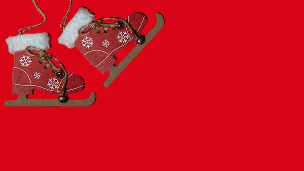 Patins de jouet de bannière de noël sur un arbre de noël sur un fond rouge isoler. espace de copie de concept de nouvel an