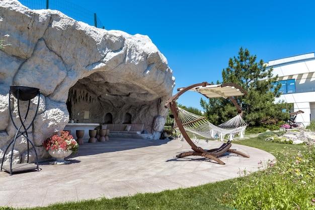 Patio équipé d'une grotte rocheuse artificielle dans un jardin verdoyant sur un domaine rural