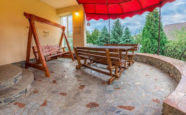 Patio de la maison familiale. table en bois avec bancs. une balançoire