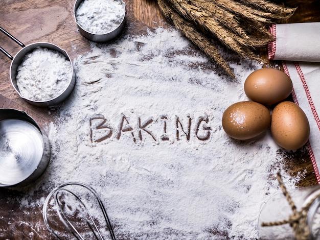 Pâtisserie accessoires de pâtisserie boulangerie avec texte de cuisson écrivant sur de la farine.