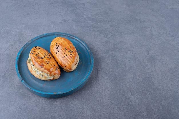 Pâtisserie au fromage sur plaque de bois sur table en marbre.