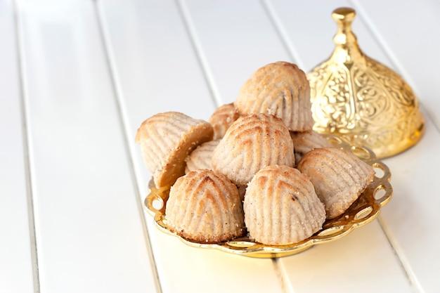 Pâtisserie ou biscuit arabe traditionnel maamoul aux dattes ou noix de cajou ou noix ou amande ou pistaches. douceurs orientales. fermer. espace en bois blanc.