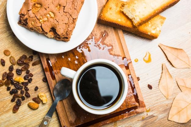 Pâtisserie et café près des raisins secs et des feuilles
