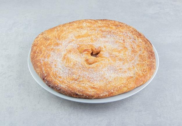 Pâtisserie circulaire décorée de poudre sur plaque blanche.