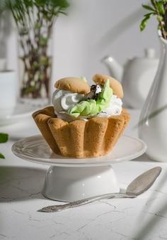 Pâtisserie et crème protéinée sur une haute assiette blanche et une cuillère sur fond blanc avec des plantes en pots