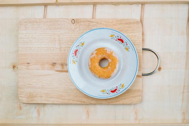 La pâtisserie est un cercle de beignets placé sur une planche.