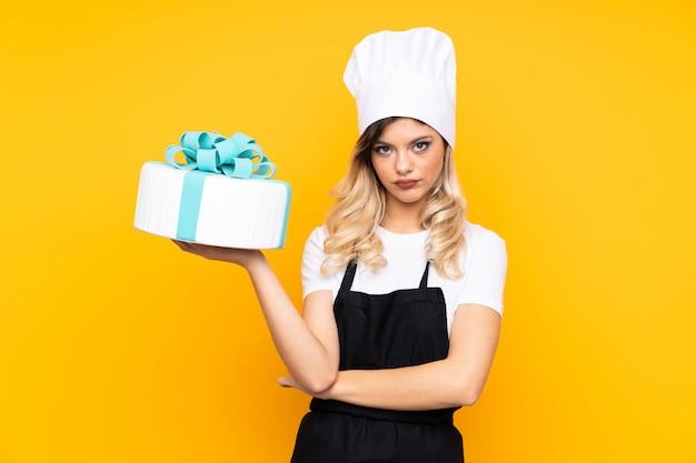 Pâtisserie fille adolescente tenant un gros gâteau sur le mur jaune en gardant les bras croisés
