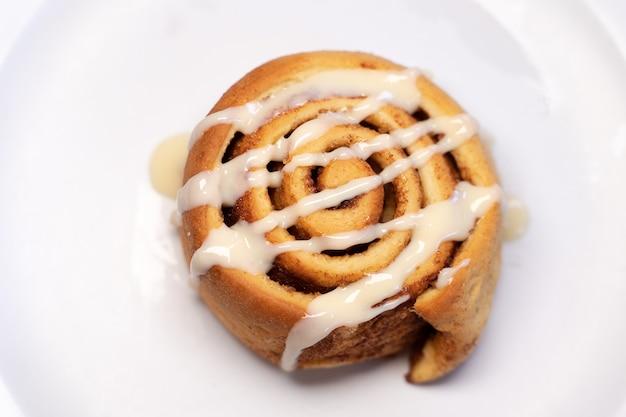 Pâtisserie en forme de spirale décorée de crème blanche sur le dessus sur fond blanc