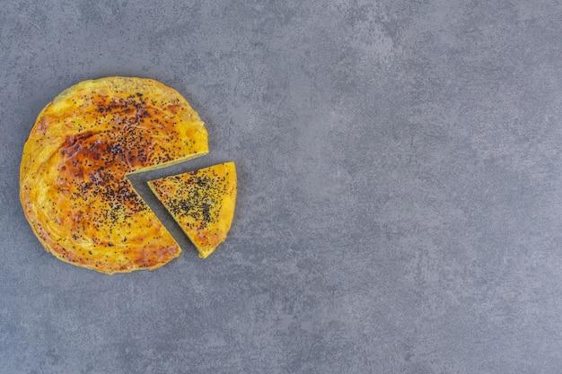 Pâtisserie fraîche aux graines de sésame noir sur table en marbre.