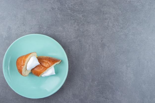 Pâtisserie fraîche à la crème sur plaque bleue.