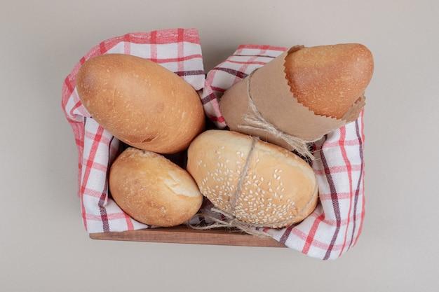 Pâtisserie fraîche de pain sur panier en bois avec nappe
