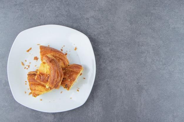 Pâtisserie fraîche tranchée sur plaque blanche.