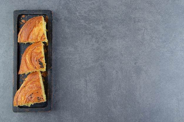 Pâtisserie fraîche tranchée sur plaque noire.