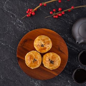Pâtisserie de jaune de gâteau de lune, gâteau de lune pour les vacances de la mi-automne, concept de design vue de dessus sur une table en bois sombre avec espace copie, mise à plat