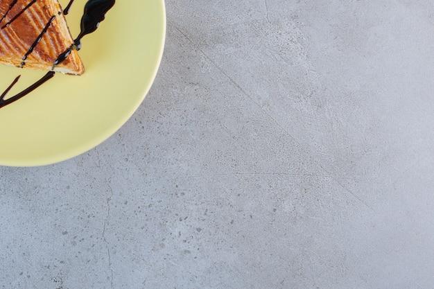 Pâtisserie maison décorée de chocolat placé sur plaque jaune.