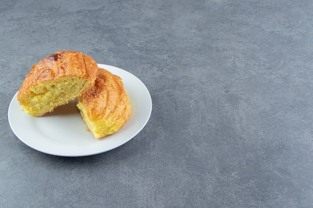 Pâtisserie maison demi-coupée sur plaque blanche.