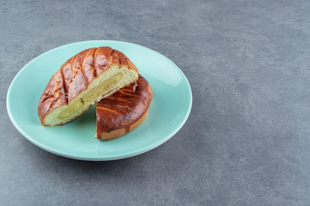 Pâtisserie maison demi-coupée sur plaque bleue.