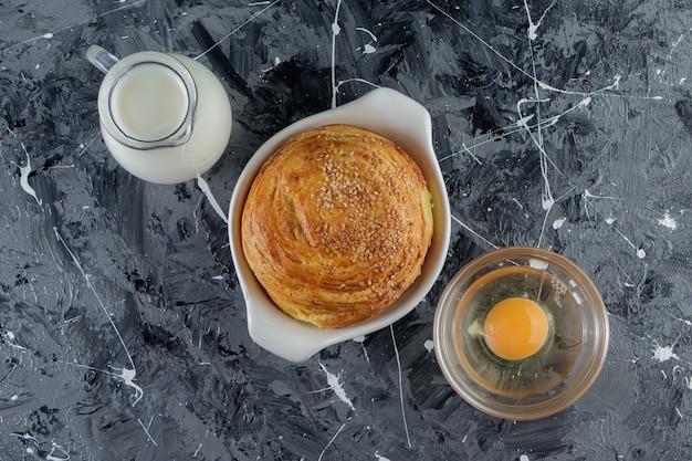 Pâtisserie nationale azerbaïdjanaise avec œuf de poule non cuit et pichet en verre de lait frais.