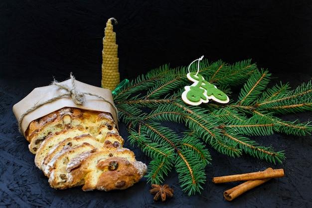 Pâtisserie de noël allemande traditionnelle - stollen sur un fond noir avec des branches de sapin, spi