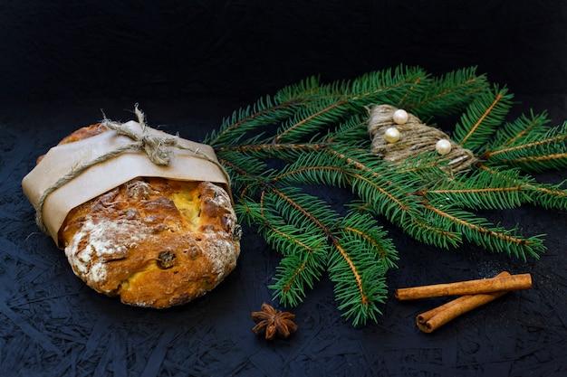 Pâtisserie de noël allemande traditionnelle - stollen sur un fond noir avec des épices de sapin
