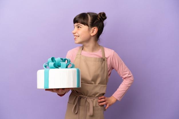 Pâtisserie petite fille tenant un gros gâteau isolé sur le côté à la recherche de violet
