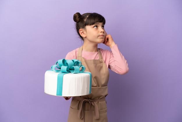 Pâtisserie petite fille tenant un gros gâteau isolé sur mur violet ayant des doutes et de la pensée
