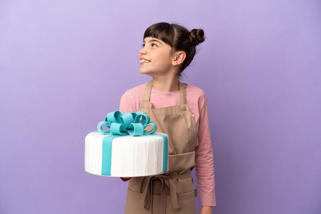 Pâtisserie petite fille tenant un gros gâteau isolé sur un mur violet à la recherche sur le côté et souriant