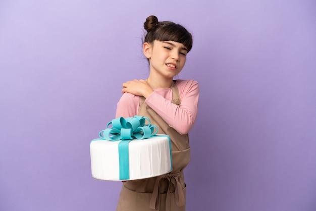 Pâtisserie petite fille tenant un gros gâteau isolé sur mur violet souffrant de douleurs à l'épaule pour avoir fait un effort