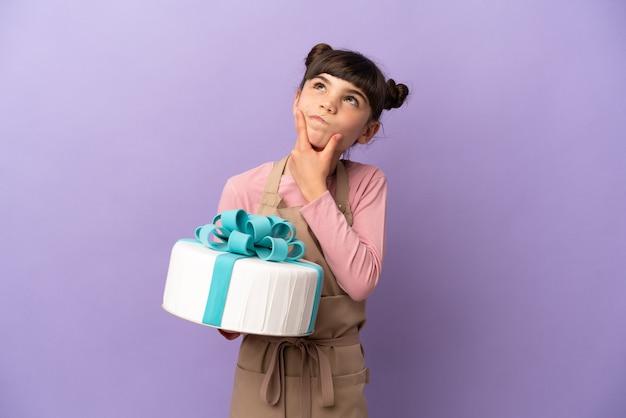 Pâtisserie petite fille tenant un gros gâteau isolé sur violet ayant des doutes
