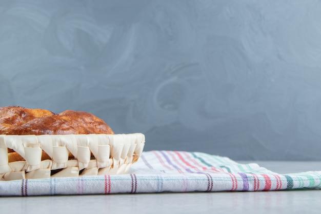 Pâtisserie ronde fraîche dans un panier en bois.