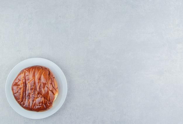 Pâtisserie ronde maison sur plaque blanche.