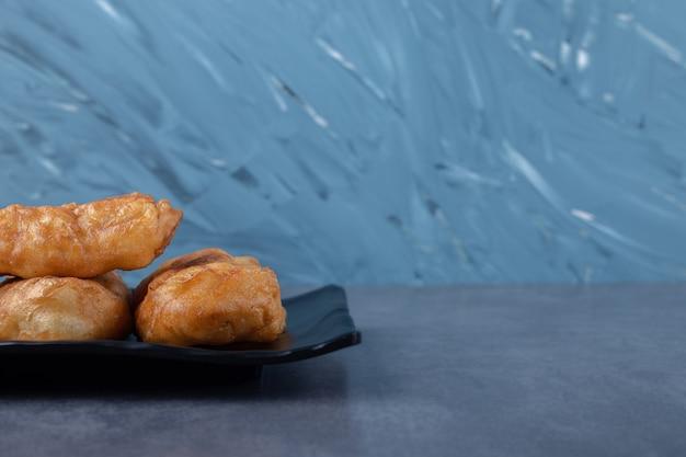 Pâtisserie russe fraîchement cuite pirozhki sur plaque de bois sur table en marbre.