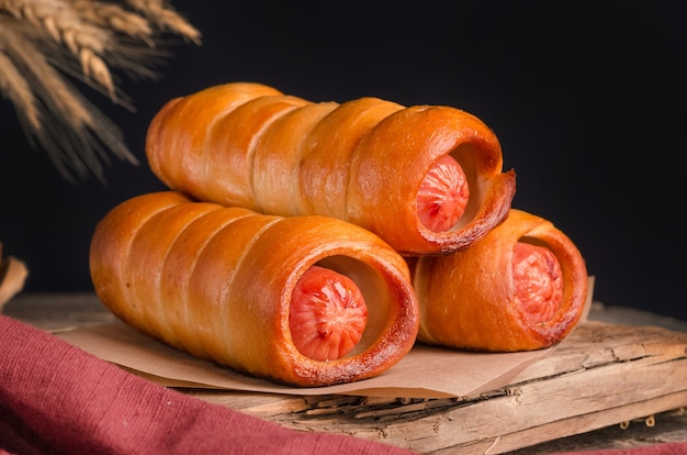 Pâtisserie de saucisses culinaires fraîches appétissantes sur fond de bois