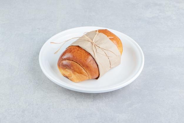 Pâtisserie savoureuse farcie sur plaque blanche.