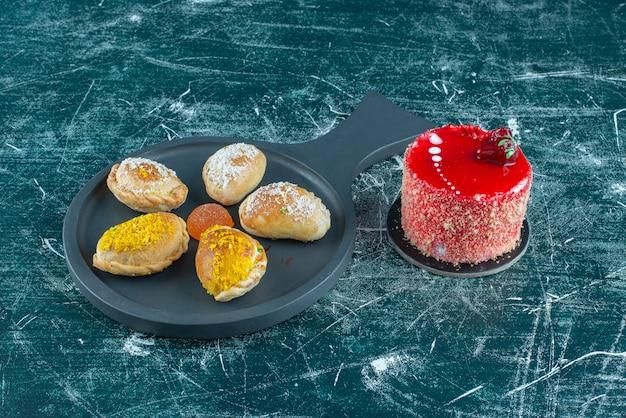 Pâtisserie servant sur un petit plateau à côté d'un petit gâteau sur bleu.